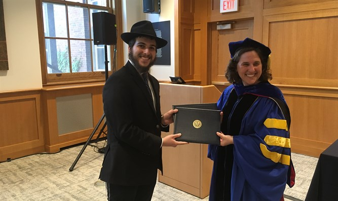 Jacob Niebloom receives his two bachelor's degrees from Dean Wendi Heinzelman