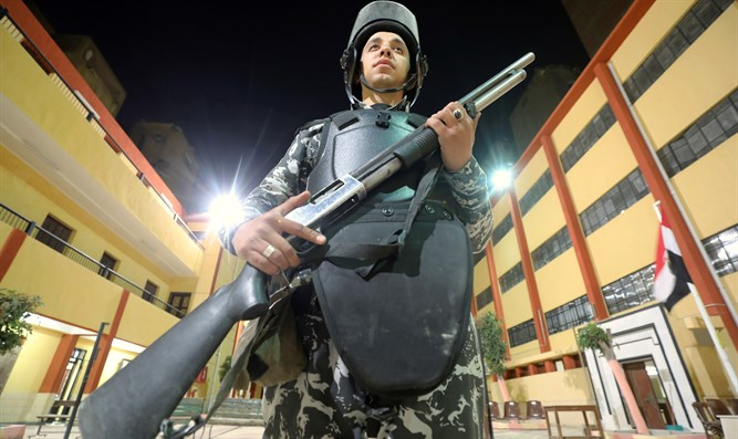 Egyptian police officer stands guard outside polling station