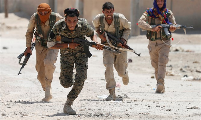 Kurdish fighters from People's Protection Units (YPG) run across street