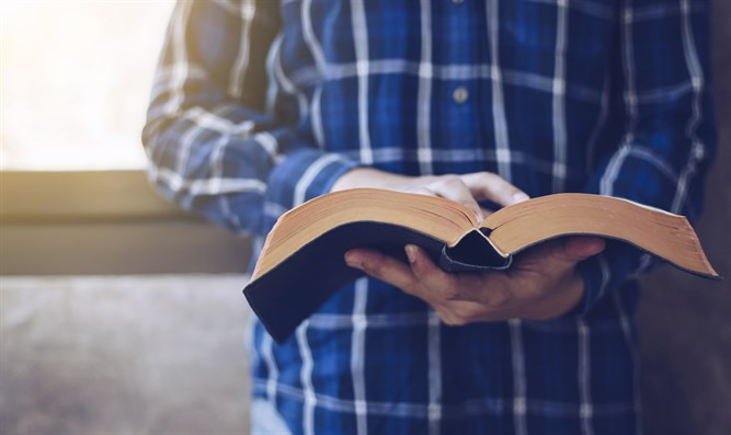 Man reading New Testament (stock)