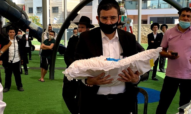 Rabbi Moshe Cohen carrying the baby